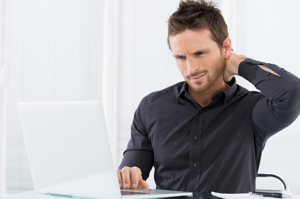 Man sitting at his desk at work with neck pain